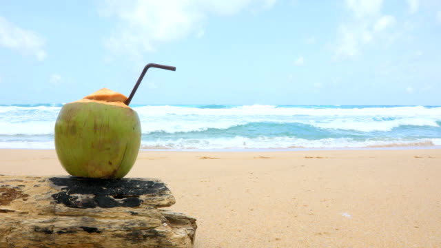 Fresh coconut with drinking straw on tropical beach, Phuket, Thailand. 4K