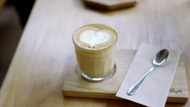 Fresh coffee served in a glass with beautiful latte art on the wooden table.