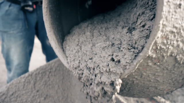 SLO MO Fresh concrete being poured out of the drum of the concrete mixer