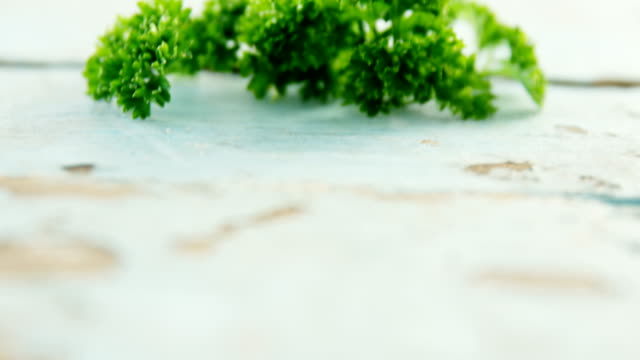 Fresh coriander leaves on wooden table 4k video