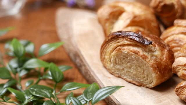 fresh croissant a flaky, viennoiserie pastry on wooden board. - cucina francese video stock e b–roll