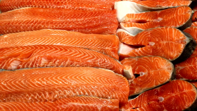 fresh fillet, chopped raw salmon, cut into pieces lies on store counter for sale. - filetto video stock e b–roll