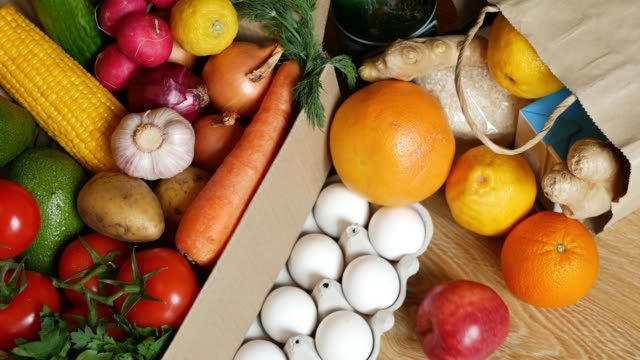 Fresh food delivery concept, quarantine covid-19 epidemic. Carton paper box packed with mixed organic vegetables close up. Container full of veggies. Delivering courier service and online shopping.