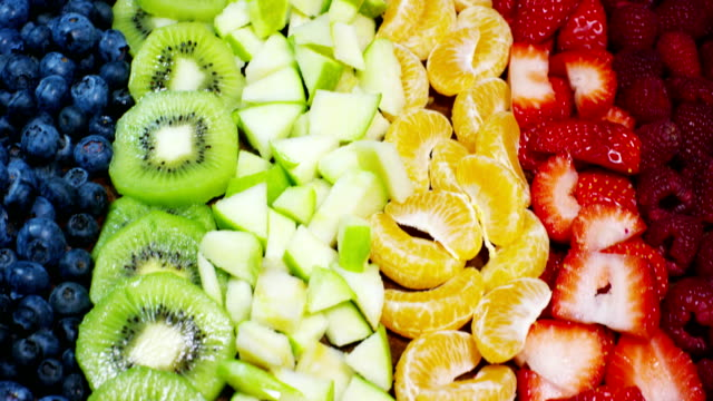 vídeos de stock e filmes b-roll de fresh fruit mix composition, with strawberry, apple,blueberry,raspberry,kiwi, orange. salad of fresh and exotic tropical fruit to eat in the summer.explosion of colors, freshness,vitamins and taste - kiwi