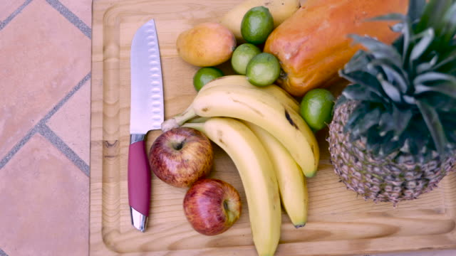 Fresh fruit on a wooden cutting board with knife shot from overhead dolly