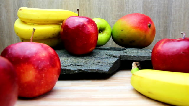 fresh fruit on kitchen desk and stone texture. apple, mango and banana fruit - icon set healthy video stock e b–roll