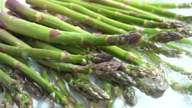 Fresh green asparagus. Water splashes. Slow motion. video