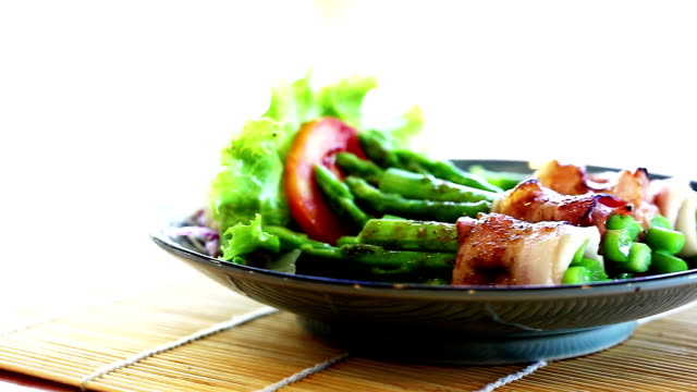 Fresh green asparagus wrapped in thick bacon. video