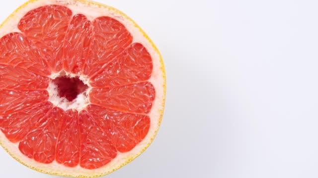Fresh half of grapefruit rotating, top view video