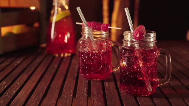 Fresh homemade lemonade with raspberries in mason jar glasses on wooden table