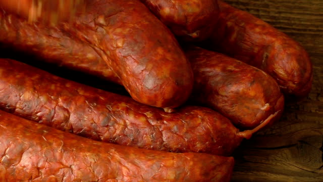 Fresh homemade sausages lying on wooden board Fresh homemade sausages lying on wooden board smokehouse stock videos & royalty-free footage