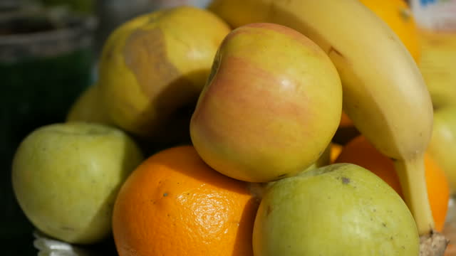 Fresh juicy fruits are on a plate. Apples, bananas and oranges are on a plate