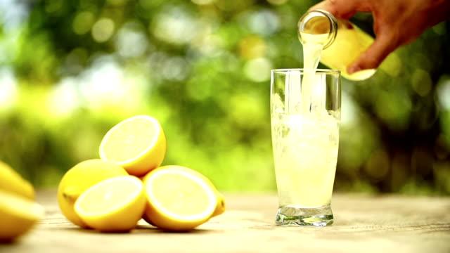 vídeos de stock e filmes b-roll de suco de limão fresco de ser vertido para vidro - limonada tradicional