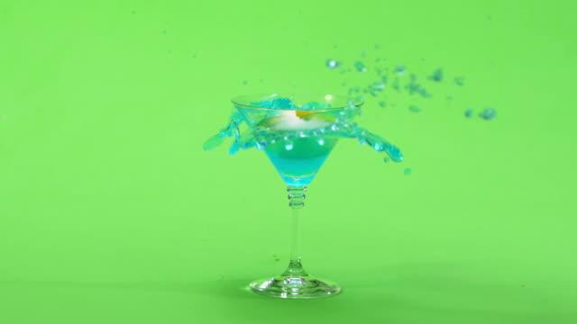 stockvideo's en b-roll-footage met een verse citroen op een cocktail stick wordt neergezet in een glas. groen scherm. - martini