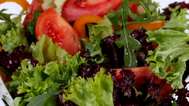 Fresh mixed vegetables falling into bowl of salad isolated on video