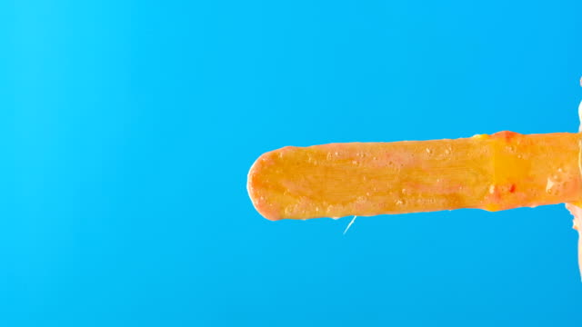 fresh orange flavor popsicle melting timelapse on a blue background please rotate it at 90 degrees to get a vertical composition - vídeo