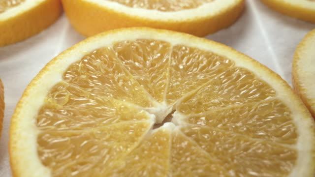 Fresh orange slices on baking paper. Close up. Slider side-to-side movement