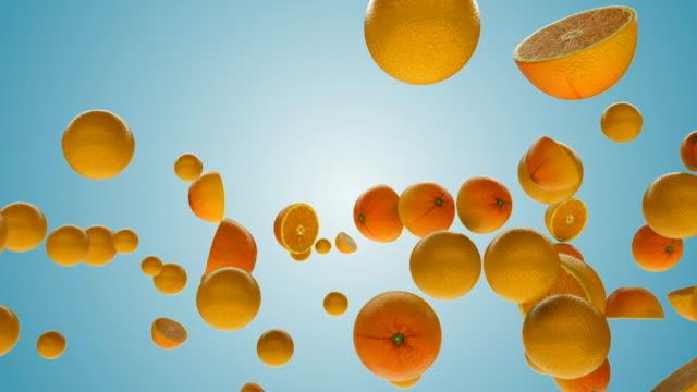 färska apelsiner flyger i slow motion mot blå lutning - apelsin bildbanksvideor och videomaterial från bakom kulisserna