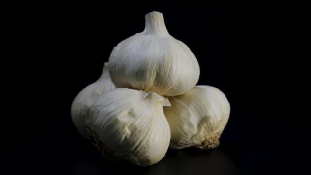 fresh organic garlic rotates against black background - aglio cipolla isolated video stock e b–roll