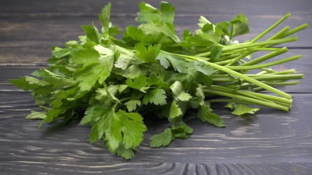 Fresh organic parsley falling on wooden background video