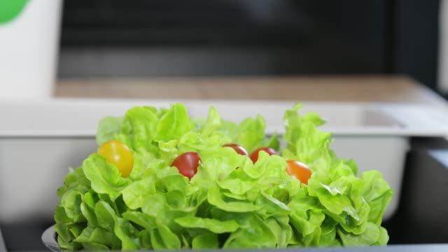 Fresh organic tomato falling on lettuce in bowl