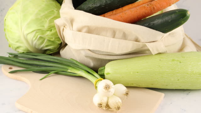 fresh organic vegetables on cutting board and in shopping bag - aglio cipolla isolated video stock e b–roll