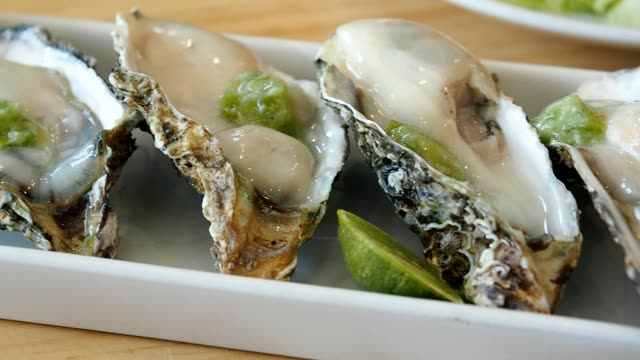 Fresh oysters on half shell with seafood sauce and lemon on a white plate. Panning left shot.