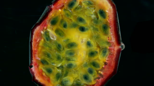 Fresh passion fruit being squeezed to reveal seeds and fresh juice video