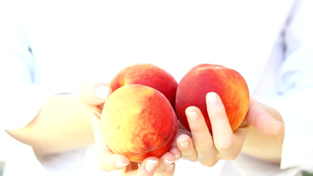 Fresh peaches in woman's hand. video