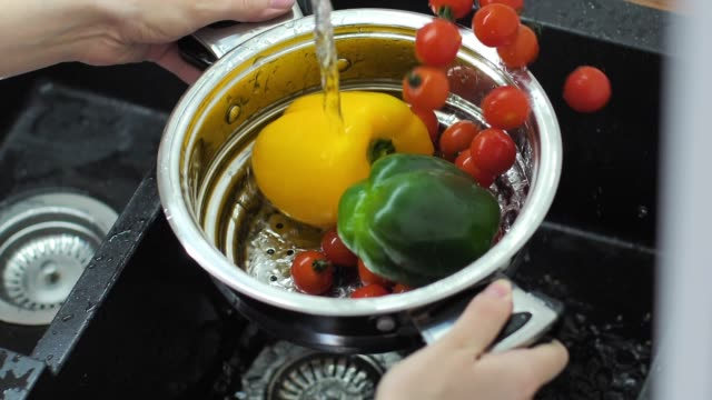 Fresh peppers splashing into water slow motion video video