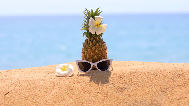 Fresh pineapple and sunglasses on tropical beach.
