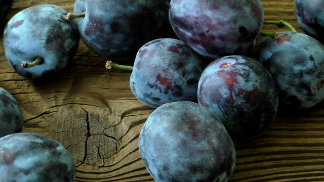 Fresh plums on wooden table video