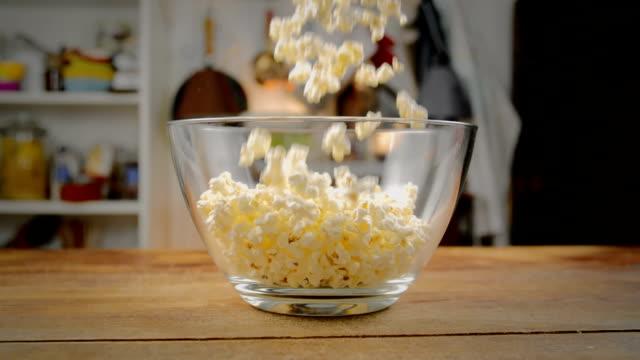 stockvideo's en b-roll-footage met verse popcorn vallen in kom - popcorn
