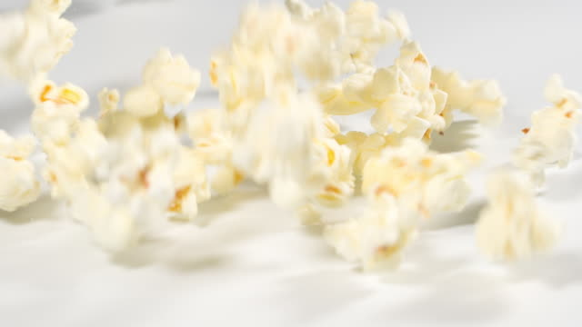 świeży popcorn spadający na białą powierzchnię w zwolnionym tempie - gotowy do jedzenia filmów i materiałów b-roll