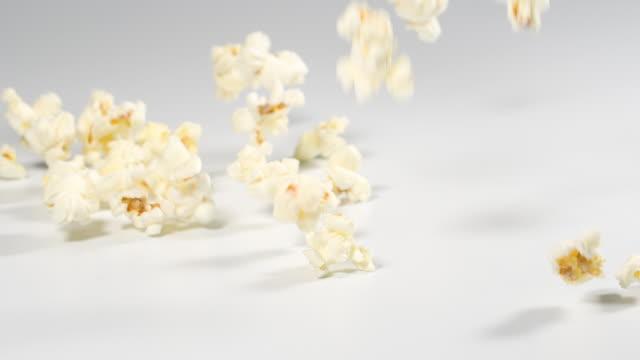 fresh popcorn falling onto a white surface in slow motion - gotowy do jedzenia filmów i materiałów b-roll