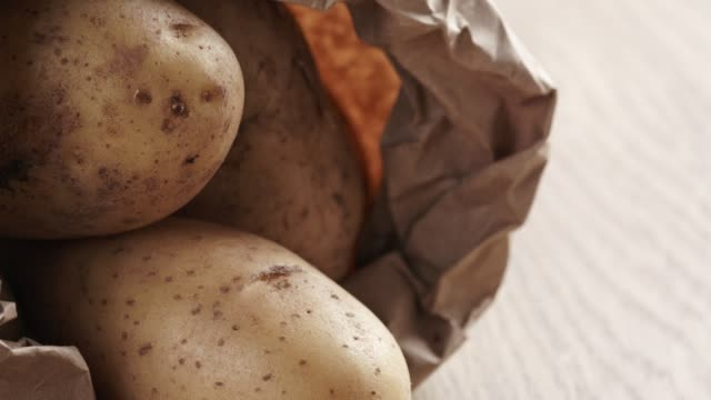 fresh potatoes in kraft paper bag on oak table - patate video stock e b–roll