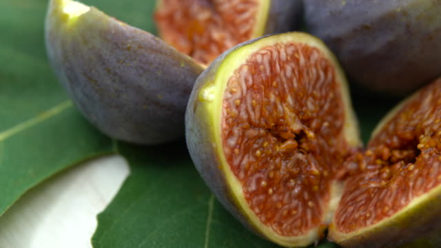 Fresh purple figs rotating on green leaves on white background. Delicious exotic berries full of vitamins. Healthy lifestyle