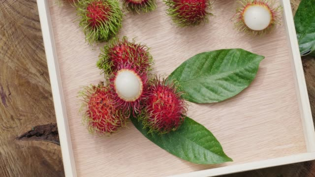 Fresh rambutan with green leaf on wooden background, relating view