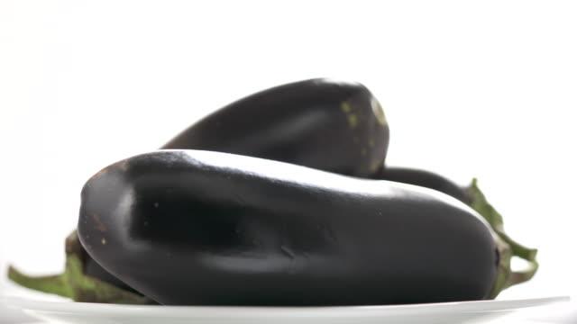 Fresh raw eggplants rotating on white background close-up.
