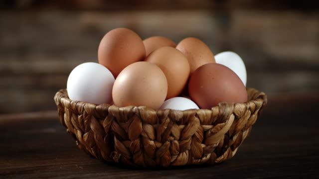 バスケットの中の新鮮な生卵はゆっくりと回転します。 - 籠点の映像素材/bロール