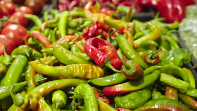 vídeos de stock e filmes b-roll de fresh raw hot green pepper in a counter of market - paprica