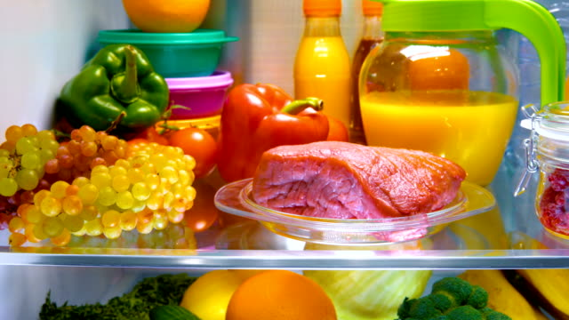 Fresh raw meat on a shelf open refrigerator video