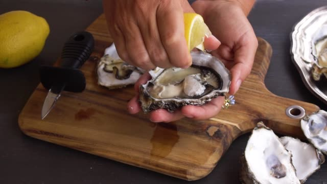 fresh raw oysters someones hands squising lemon on fresh raw oysters peeled stock videos & royalty-free footage
