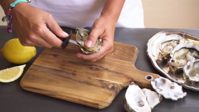 fresh raw oysters someones hands open fresh raw oyster shell peeled stock videos & royalty-free footage