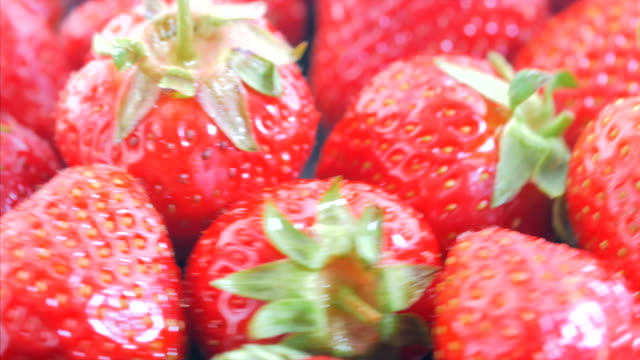 Fresh, ripe, juicy strawberries rotate. Red strawberries clockwise rotation. Appetizing berries with droplets rotate on a tray video