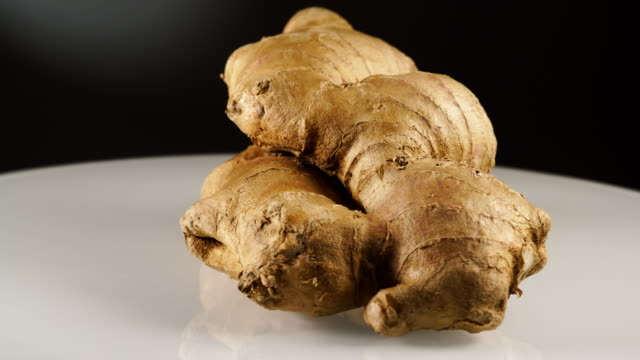 Fresh root ginger on plate Fresh ginger root on white plate, black background. Healthy eating ginger spice stock videos & royalty-free footage