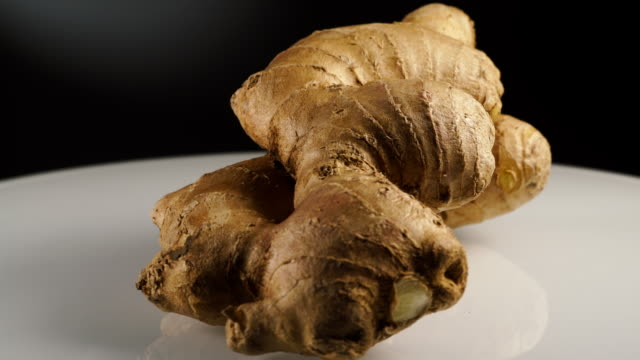 Fresh root ginger rotating on plate Fresh ginger root on white plate, black background. Healthy eating ginger spice stock videos & royalty-free footage