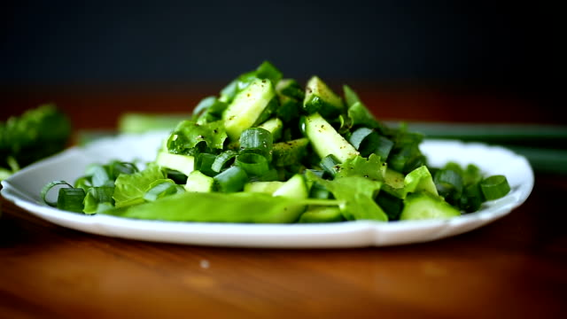 fresh salad of cucumbers and greens in a plate on a wooden