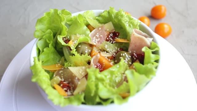 insalata fresca di lattuga, pomodorini, olive, pomodori secchi, prosciutto di parma, formaggio cheddar, parmigiano, olio d'oliva e sesamo. concetto di alimentazione sana. - crudo video stock e b–roll