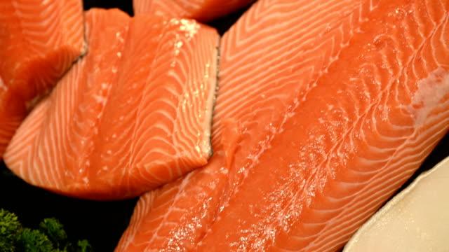 vídeos de stock e filmes b-roll de 4k fresh salmon fillet on supermarket counter - meat texture